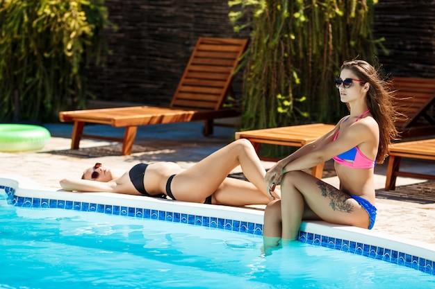 Young beautiful women smiling, sunbathing, relaxing near swimming pool