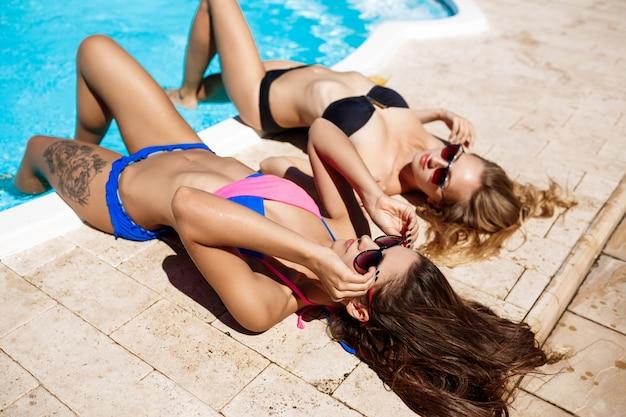 Young beautiful women smiling, sunbathing, relaxing near swimming pool.