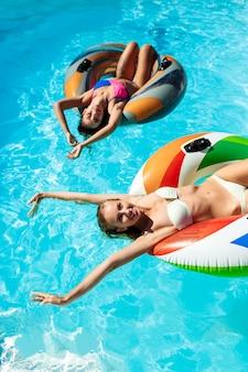 Giovani belle donne che sorridono, prendendo il sole, rilassandosi, nuotando nello stagno