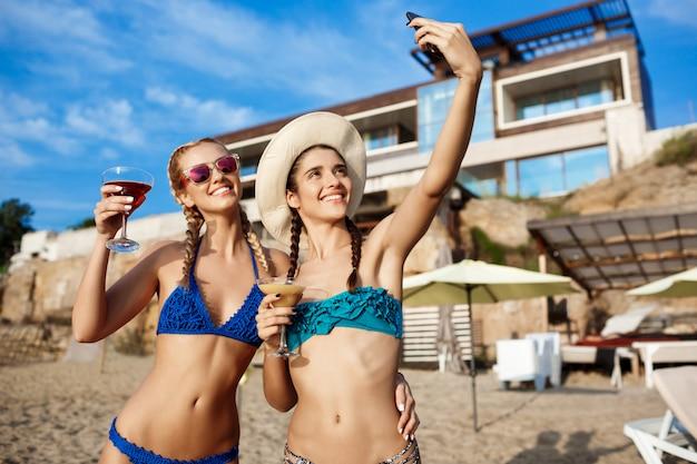 Young beautiful women in swimwear smiling, making selfie at beach