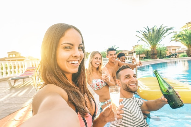 Young beautiful women taking a selfie with her friends making pool party drinking champagne