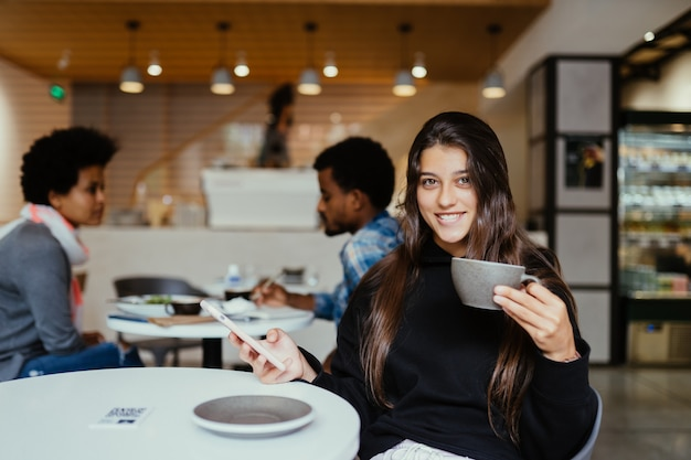 Young beautiful women using smartphone, charming female student sitting in cafe