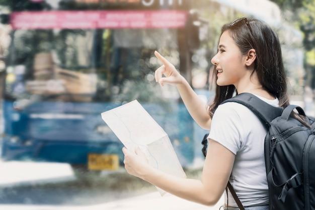 Молодые красивые женщины с рюкзаком держа карту и гуляя в город.