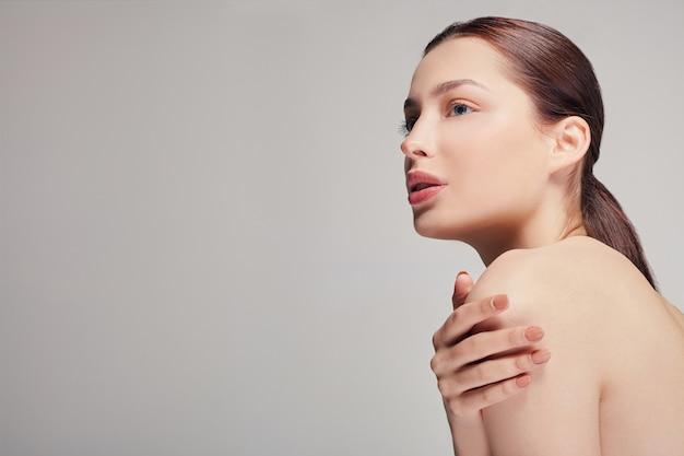 Молодая красивая женщина с темными волосами сидит боком обнимает себя за плечи