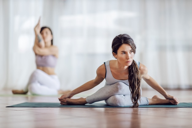 Young beautiful yogi girls doing yoga. girl in front is in extended bound lotus yoga pose while other one doing variation.
