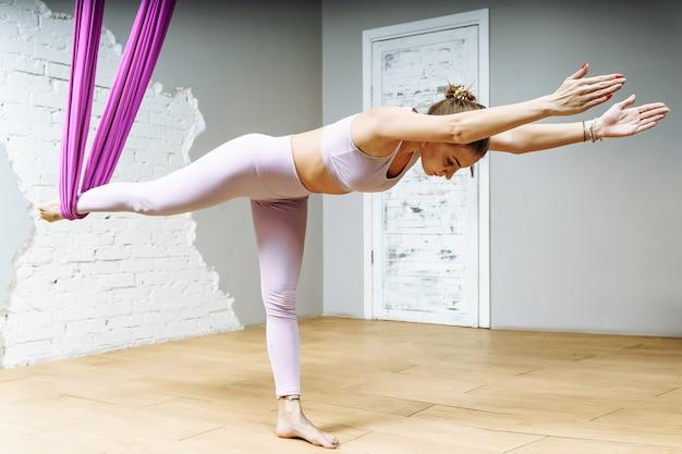 피트니스 클럽에서 보라색 해먹에서 공중 요가 연습을 하는 젊은 아름다운 요기 여성