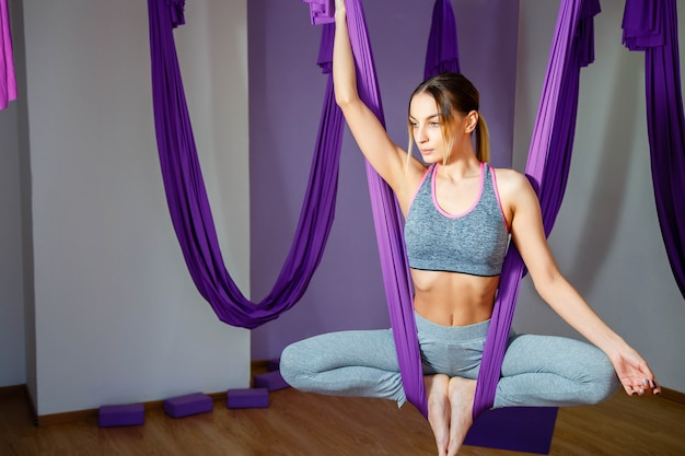 Young beautiful yogi woman doing aerial yoga practice in purple hammock in fitness club.