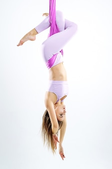 Young beautiful yogi woman doing aerial yoga practice in purple hammock.