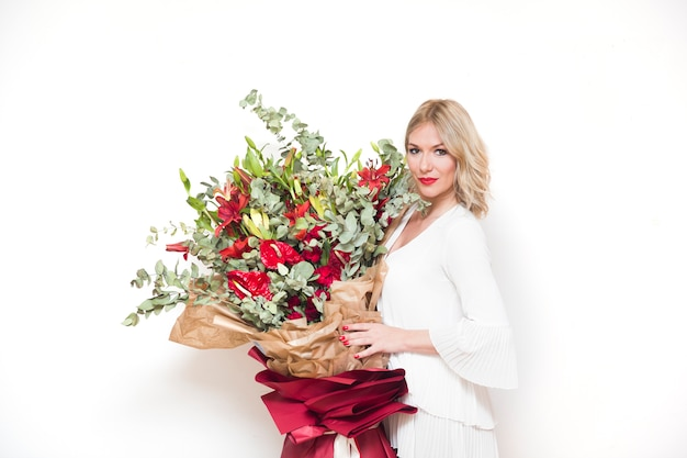 Young beautifull blond woman holding big bouquet of colorful flowers against the wall