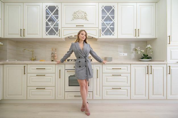 Молодая красивая женщина на бежевой кухне