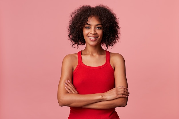 Young beauty african american lady with curly dark hair , wearing red t-shirt, smiling and looking with arms crossed isolated.