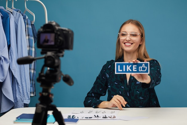 Young beauty blogger asking to like her content while talking with people online
