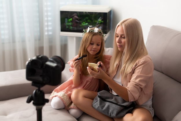 Young beauty blogger and her sweet daughter recording video at home