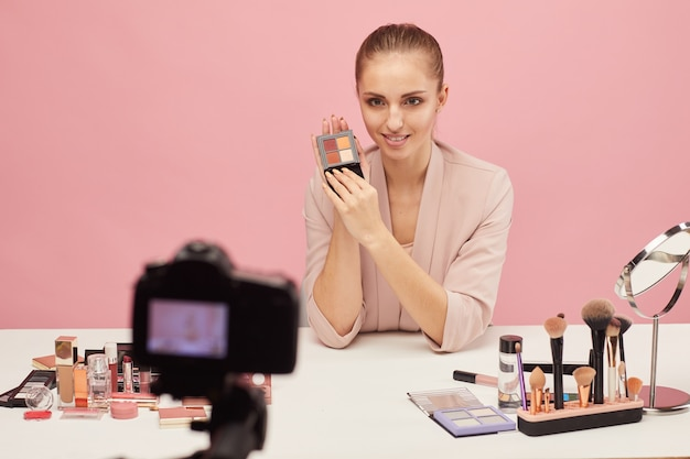 Юная бьюти-блогерша сидит за столом и рассказывает о декоративной косметике на камеру для своих подписчиков