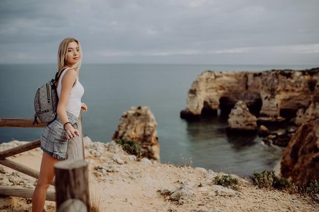Молодая блондинка красоты путешественник женщины смотря море и утес на красивом пляже португалии.
