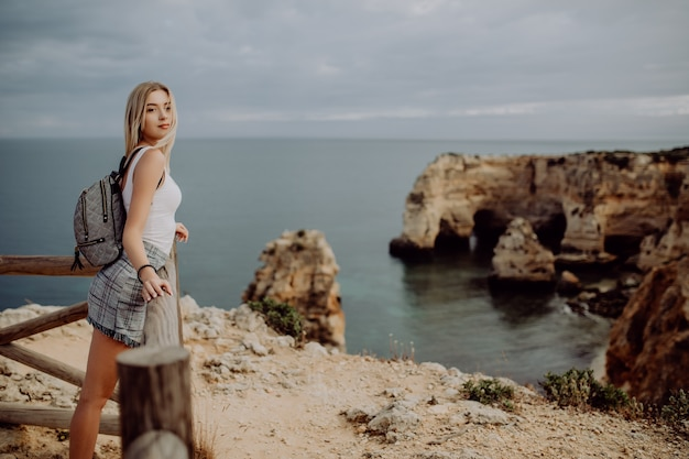 Young beauty blonde woman traveler looking at the sea and cliff on beautiful portugal beach.