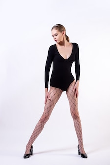 Young beauty blondy woman posing in black body, pantyhose and high heels on white