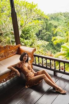 젊은 아름다움. 발리에서 겨울 방학을 보내는 동안 긍정적인 표정을 하는 갈색 머리 여성