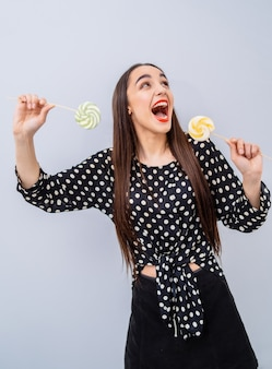 Young beauty in dotted shirt with two lollipops in hands. cheerful lady with candies over white background.