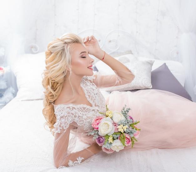 Молодая невеста моды красоты в зимнем декоре с букетом цветов в ее руках.