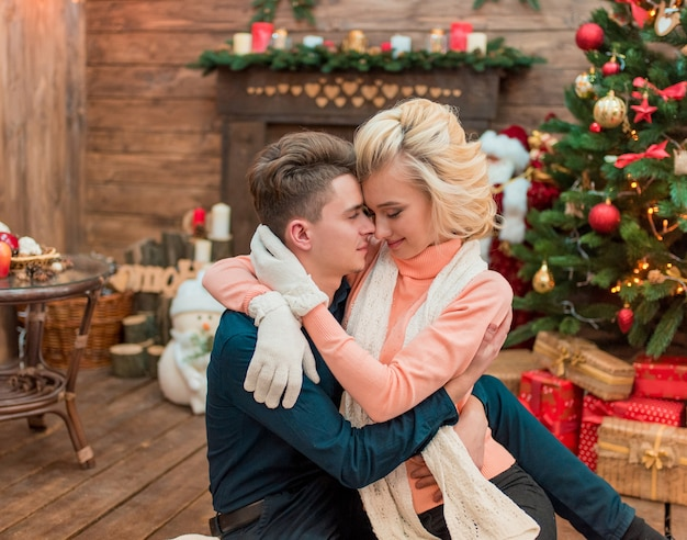 Молодая невеста моды красоты зимой счастливые влюбленные пары поздравляют друг друга с рождеством. украшенная рождественская елка, праздник и новогодняя концепция.