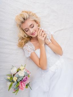 彼女の手に花の花束とベッドの装飾の若い美容ファッション花嫁。美しい花嫁の肖像画の結婚式のメイクや髪型。ゴージャスな美しさの花嫁。
