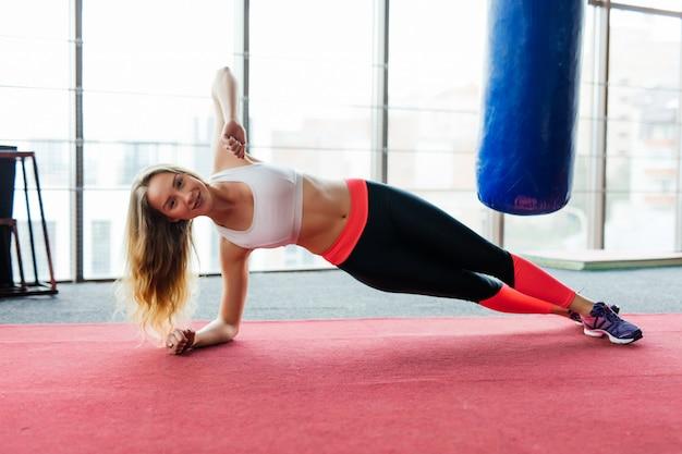 Giovane bellezza fitness donna in piedi in plancia in palestra al chiuso