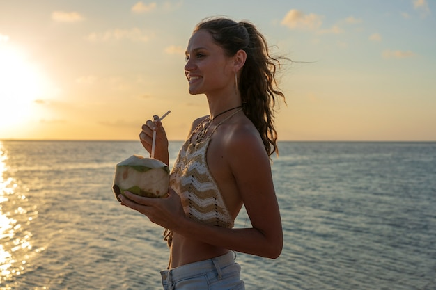 Young beauty girl drinking coconut at tropical beach near sea water at paradise island at sunset, close up. summer concept. holiday travel.