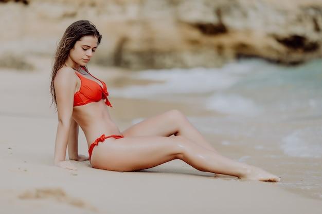 Молодая девушка красоты в красном бикини, сидя на золотом песке, наслаждается призванием океана.