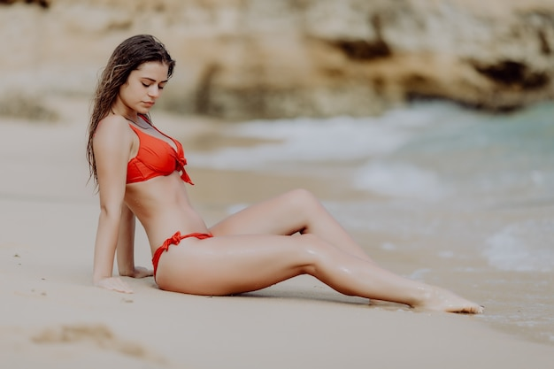 Young beauty girl in red bikini sitting on golden sand enjoy ocean vocation.