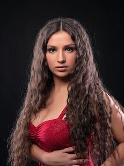 Молодая красотка с удивительными вьющимися волосами красного цвета