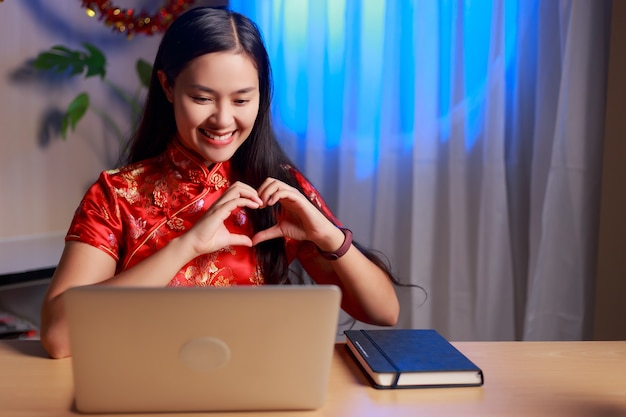 Young beauty happy asian woman wearing chinese tradition dress making video conference making heart shape hands telling love and celebrating chinese new year at home.