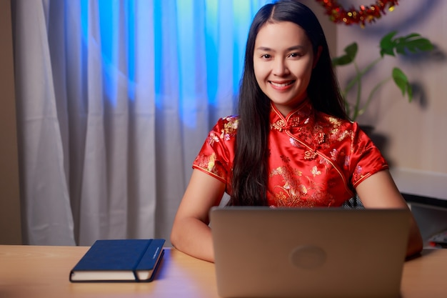 Young beauty happy asian woman wearing chinese tradition dress sitting in front of laptop with smiley face celebrating chinese new year at home.