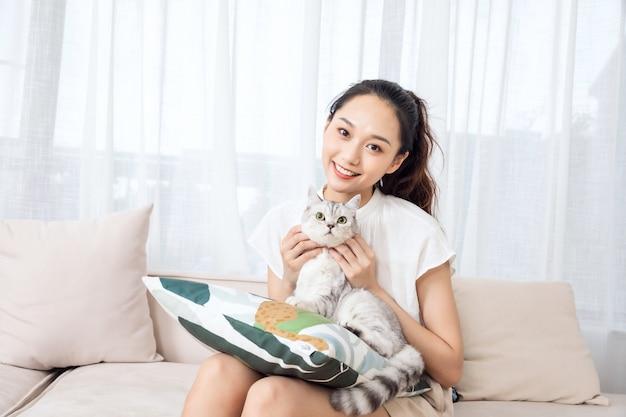 Молодая красавица лижет кошку дома
