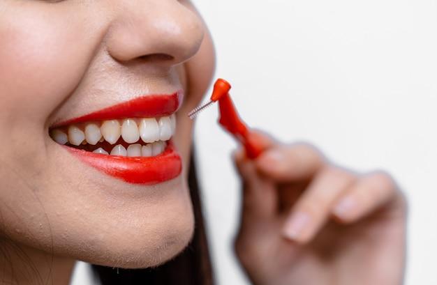 Молодая красавица с красными губами и идеальными зубами держит зубную щетку. обрезанное фото.