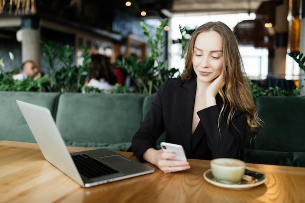 カフェテリアでの若い美しさの女性はノートパソコンと電話で話し、コーヒーを飲みます。