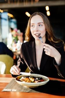 Giovane donna di bellezza che mangia piatto di insalata al negozio di caffè