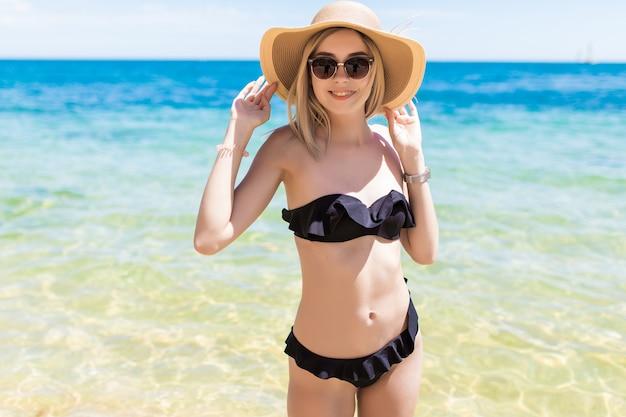 La giovane donna di bellezza in cappello e occhiali da sole gode dell'acqua fresca sulla spiaggia