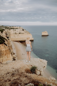 Молодая красавица женщина в соломенной шляпе, наслаждаясь прекрасным видом на скалистое побережье во время восхода солнца