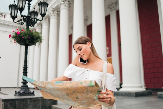 Young beauty woman tourist explore city map and talking on phone in urban environment against columns