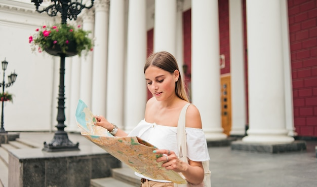 Young beauty woman tourist explore city map in urban environment against columns