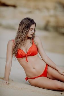 Молодая красавица женщина с идеальным телом в красном бикини, лежа на пляже над морем