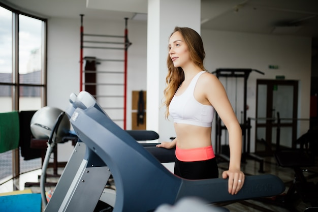 Young beauty woman working out on run simulator in sport gym club.