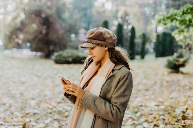 秋の公園で携帯電話でメッセージを書く若い美容女性