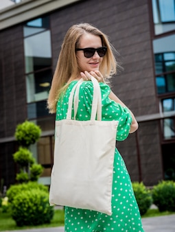 Young beautyful woman with linen eco bag on city background