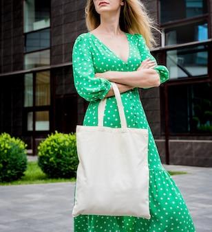 街の背景にリネンエコバッグを持つ若い美しい女性