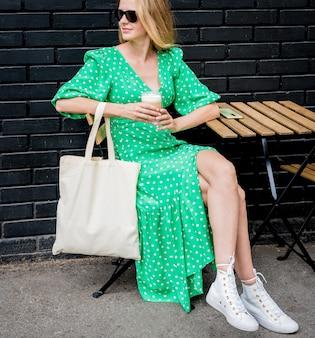 Молодая красивая женщина с льняной эко-сумкой на фоне города