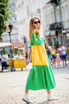 Молодая красивая женщина с желтой льняной эко-сумкой на фоне города