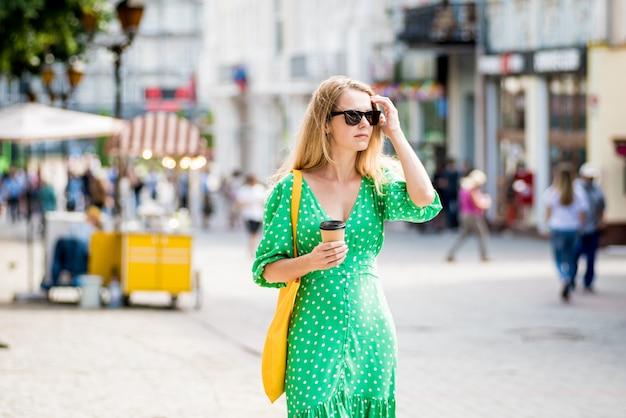 도시 배경에 노란색 린넨 에코백을 든 젊은 미녀