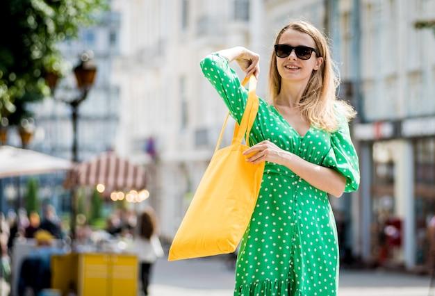 街の背景に黄色のリネンエコバッグを持つ若い美しい女性